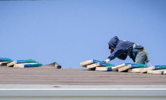 One of Presto Roofing's roofers on a commercial project